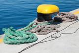 Yellow mooring bollard and nautical ropes