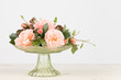 Pink garden rose arrangement in green glass pedestal vase.