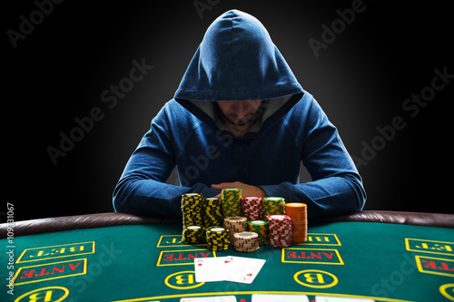 Portrait of a professional poker player sitting at pokers table плакат