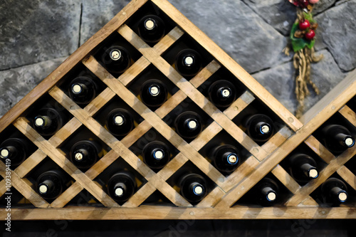 Wine bottles stacked on wooden racks © haveseen
