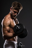 Handsome young bodybuilder training withdumbbells, on grey