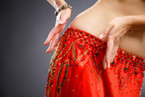 Fototapety Beautiful belly dancer young woman in gorgeous red and green costume dress. Part of body