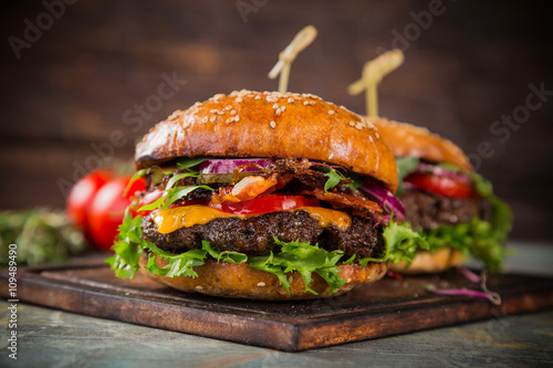 Tasty burgers on wooden table. - 109489490