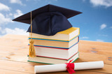 close up of books with diploma and mortarboard