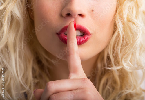 Woman holding her finger pressed against her lips Poster