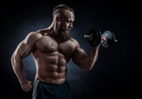 Power athletic bearded man in training pumping up muscles with d