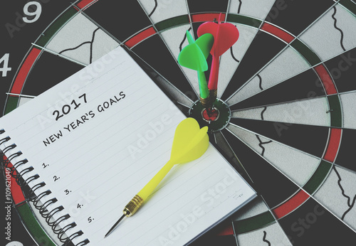 Poster 2017 new year's goals on notepad with darts on bulls eye, retro style