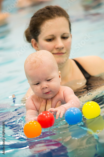 baby girl enjoying her first swim with her mom Poster