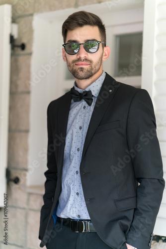 Sexy man in tuxedo posing плакат