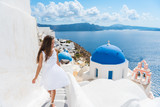 Santorini travel tourist woman on vacation in Oia walking on stairs. Person in white dress visiting the famous white village with the mediterranean sea and blue domes. Europe summer destination