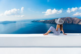 Fototapety Europe Greece Santorini travel vacation. Woman looking at view on famous travel destination. Elegant young lady living fancy jetset lifestyle wearing dress on holidays. Amazing view of sea and Caldera