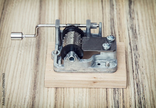 Old little music box on the wooden background, retro style Poster