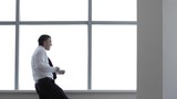 Happy Businessman Dances with Joy/The businessman dances with joy in front of a big window