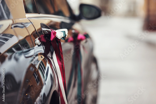 Black car handle decorated with ribbons Poster