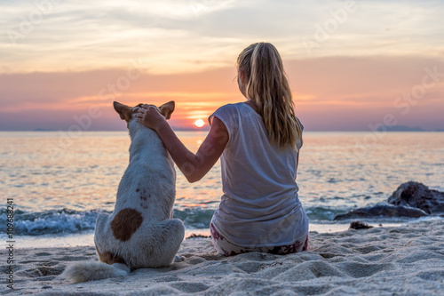 Poster Young woman with dog sitting on the beach and watching the sunset