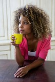 Thoughtful woman holding a cup of coffee in kitchen