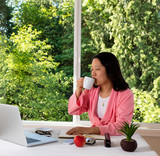 Mature woman enjoying her coffee in the morning while working