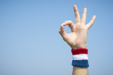 Hand of an athlete making OK sign with finger and thumb against blue sky wearing a red white and blue sport wristband