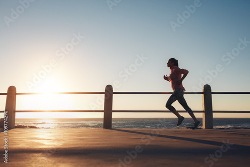 Poster Sportswoman running on a road by the sea