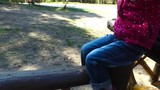 A child girl goes on a wooden log. Girl child running around on the playground in the park. Children having fun outdoors. Sunny spring day.