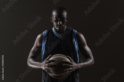 Plexiglas Basketbal Portrait of basketball player holding a ball