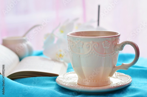 Plakat A cup of coffee, open book and flowers on a blue tablecloth