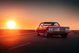 Retro red car standing on asphalt road at sunset