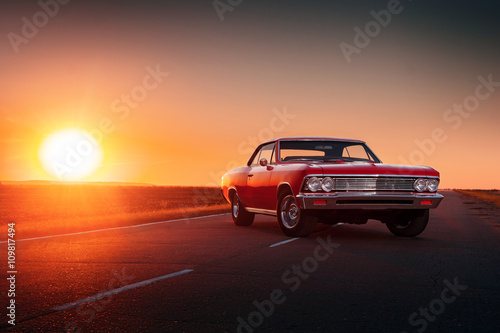 obraz lub plakat Retro red car standing on asphalt road at sunset