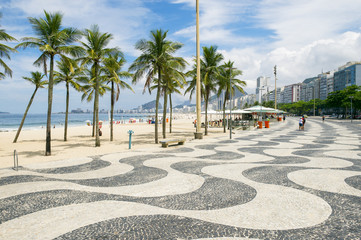 The iconic sidewalk tile pattern of Copacabana Beach curving off into the Rio de Janeiro, Brazil skyline