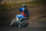 Fototapety motorcycle racer on a motorcycle rides in turn a dusty track during competition racing