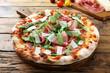 pizza con prosciutto rucola e parmigiano sfondo tavolo legno rustico