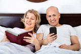 Positive cheerful  mature couple together social networking