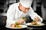 Fototapety Concentrated male chef garnishing food in kitchen
