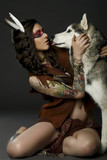 Beautiful woman in native american costume posing in a studio with hasky dog