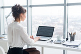 Young businesswoman working in office, typing, using computer. Concentrated woman searching information online, rear view portrait.