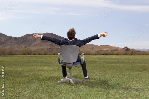 Businessman sitting on chair on green meadow