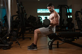 Man In The Gym Exercising Biceps With Dumbbell