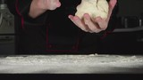 SLOW: A cook kneads a dough on a cutting board in a kitchen