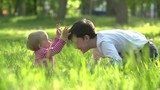 Boy Plays with the Happy Little Sister in Park