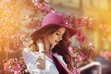Outdoor portrait of young beautiful happy smiling lady posing near flowering tree. Model wearing stylish accessories & clothes. Girl closed her eyes. Female beauty & fashion concept. City lifestyle
