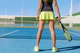 Tennis player woman in skirt holding racket wearing neon yellow skort outfit and running shoes. Lower body crop of sexy legs for fitness and weight loss concept. Summer outdoor blue hardcourt.