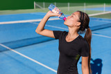 Healthy tennis player thirsty thirst quenching drinking health sports drink water plastic bottle hydrating before playing a game on blue hardcourt. Professional athlete living an active fit lifestyle.