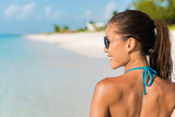 Happy beach lifestyle sunglasses girl smiling having fun. Beautiful Asian bikini woman relaxing on sunset tropical vacation view from back living a fit healthy lifestyle. Suntan skin body care.