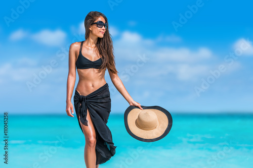 Elegant beach woman in bikini and fashion sarong standing on shore. Sexy lady in black beachwear, floppy hat, sunglasses enjoying sun on tropical destination during summer vacation in the Caribbean. © Maridav