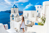 Santorini travel tourist woman on vacation in Oia walking on stairs. Lovely girl in white dress visiting the famous white village with the mediterranean sea and blue domes. Europe summer destination.