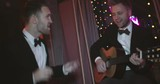 Two men in tuxedo singing a song together at party: one man playing a guitar and giving high five to his friend