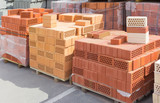 Several pallets of perforated bricks different colors with round