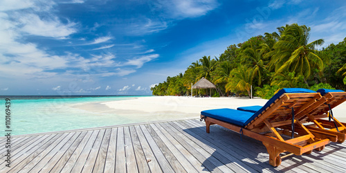 Poster sun lounger bed on jetty in front of paradise island and beach / Sonnenliege auf