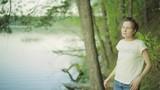 Красивая девушка спускается на берег озера, смотрит вдаль