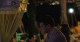 Young man sitting alone in street cafe at night and using smart phone. Lonely summer evening